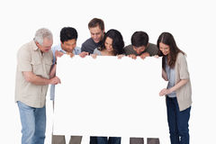 Group looking at blank sign in their hand Royalty Free Stock Photo