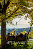 Group of Male and Female Seniors Sitting on Bench with View in Autumn Royalty Free Stock Photography