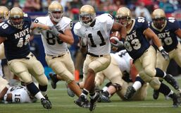 Group of Male Football Players Running on Field during Day Royalty Free Stock Photos