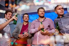 Group of male friends with beer in nightclub. Nightlife, party, friendship, leisure and people concept - group of smiling male friends with beer bottles drinking Stock Image