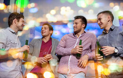 Group of male friends with beer in nightclub. Nightlife, party, friendship, leisure and people concept - group of smiling male friends with beer bottles drinking Royalty Free Stock Photos