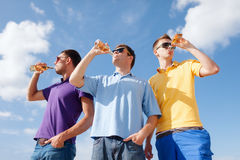 Group of male friends with bottles of beer. Summer, holidays, vacation, happy people concept - group of male friends having fun on beach with bottles of beer or Royalty Free Stock Photography