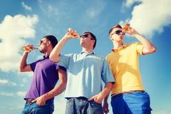 Group of male friends with bottles of beer. Summer, holidays, vacation, happy people concept - group of male friends having fun on beach with bottles of beer or Stock Photos