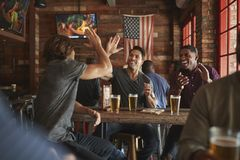 Group Of Male Friends Celebrating Whilst Watching Game On Screen In Sports Bar stock image