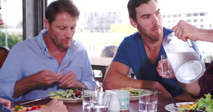 Group Of Male Friends Enjoying Meal In Restaurant Together. Camera tracks around group of men sitting around table at rooftop restaurant - one pours water from a stock footage