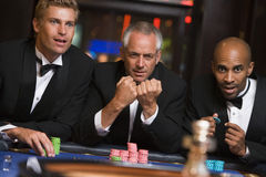 Group of male friends gambling at roulette table. In casino Royalty Free Stock Photo