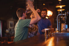 Group of male friends giving high five to each other. Group of male friends watching football match in pub Stock Photo