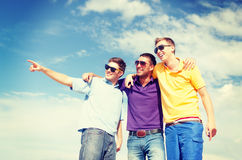 Group of male friends walking on the beach. Summer, holidays, vacation, happy people concept - group of male friends walking on the beach pointing finger Royalty Free Stock Photo