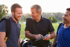 Group Of Male Golfers Marking Scorecard At End Of Round Royalty Free Stock Photo