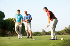Group Of Male Golfers Teeing Off. On Golf Course royalty free stock image