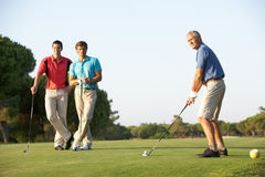 Group Of Male Golfers Teeing Off. On Golf Course royalty free stock photos