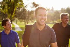 Group Of Male Golfers Walking Along Fairway Carrying Bags Stock Image