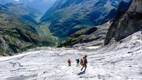 Group of male mountain climbers crossing a glacier on their way down from a high alpine peak. A group of male mountain climbers crossing a glacier on their way Royalty Free Stock Images