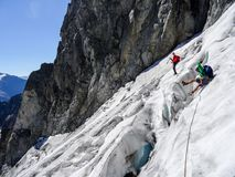 Group of male mountain climbers crossing a glacier on their way down from a high alpine peak royalty free stock image