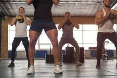 Small Group of Muscular Male Adults Working Out With Kettlebells royalty free stock images