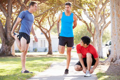 Group Of Male Runners Warming Up Before Run Stock Photo