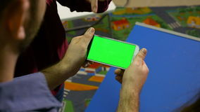 Group of man and woman watching a smart phone with green screen and pointing at something stock footage