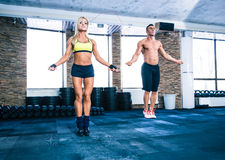 Group of a man and woman workout with jumping rope. Muscular men and beautiful sporty women workout with jumping rope in crossfit gym Stock Photography