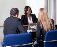 Group of managers interviewing female candidate. Group of managers interviewing pretty young female candidate for job at the office stock photos
