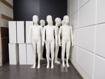 Group of manikin boys in store. Group of white plastic fashion shop mannequin of child or boy naked without clothes stand up stored huddled in corner of Stock Photo