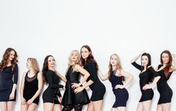 Group of many cool modern girls friends in diverse fashion style black dress  together having fun isolated on whit Stock Photos
