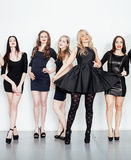 Group of many cool modern girls friends in diverse fashion style black dress together having fun isolated on white Stock Photos