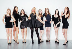 Group of many cool modern girls friends in diverse fashion style black dress together having fun on white. Background, happy smiling lifestyle people concept stock photography
