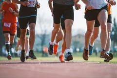 Group of marathon racers runningon the track stock photos