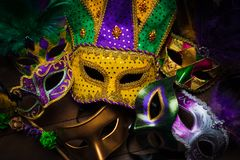 A group of mardi gras, carnivale mask on a dark background. A group of carnivale or mardi gras mask with a yellow jester on a dark background stock photography