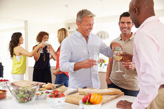 Group Of Mature Friends Enjoying Dinner Party At Home Stock Photography