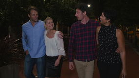 Group Of Mature Friends Walking Along Street On Night Out. Group of mature friends walking towards camera on night out in city.Shot in 4k on GH4 at frame rate of stock video footage