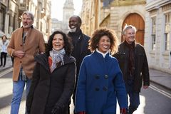 Group Of Mature Friends Walking Through City In Fall Together royalty free stock photography