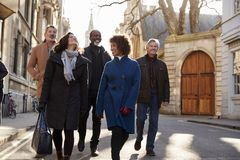 Group Of Mature Friends Walking Through City In Fall Together stock photography