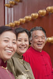 Group of mature people in traditional clothes standing next to traditional Chinese door, portrait Stock Photo