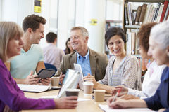 Group Of Mature Students Collaborating On Project In Library Royalty Free Stock Image
