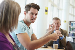 Group Of Mature Students Collaborating On Project In Library Stock Photo