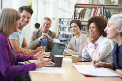 Group Of Mature Students Collaborating On Project In Library royalty free stock images