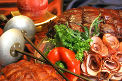 Group of meat on holiday table with candle and sword Stock Image