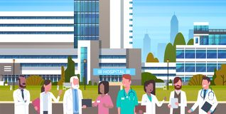 Group Of Medical Doctors Standing In Front Of Hospital Building Exterior. Flat Vector Illustration royalty free illustration