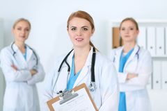 Group of medical doctors standing at hospital. Team of physicians ready to help patients. Medicine and health care. Concept royalty free stock photography