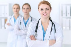 Group of medical doctors standing at hospital. Team of physicians ready to help patients. Medicine and health care. Concept stock photography