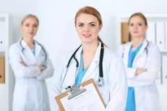 Group of medical doctors standing at hospital. Team of physicians ready to help patients. Medicine and health care. Concept stock photos