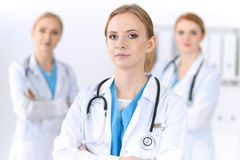 Group of medical doctors standing at hospital. Team of physicians ready to help patients. Medicine and health care stock photos