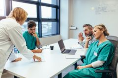 Group of medical professionals brainstorming in meeting. Group of medical professionals brainstorming in a meeting. Team of healthcare workers discussing in stock photos