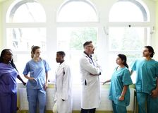 Group of medical professionals discussing in the hallway of a hospital stock photo