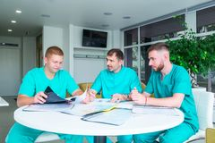 Group of medical staff discussing patient results in clinic. Healthcare professionals having discussion in hospital. Experienced. Doctor explaining smth and stock photos