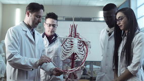 Group of medical students at an anatomy lecture. Group of diverse young interns or medical students at an anatomy lecture with a doctor demonstrating the stock video footage
