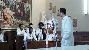 Group of medical students at an anatomy lecture. Group of diverse young interns or medical students at an anatomy lecture with a doctor demonstrating the stock video