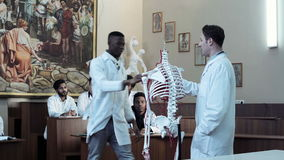 Group of medical students at an anatomy lecture. Group of diverse young interns or medical students at an anatomy exam. Doctor asking to african student raised stock video
