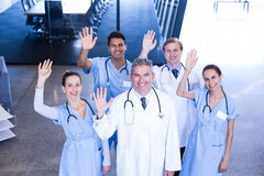 Group of medical team standing with their hand raised Stock Photos